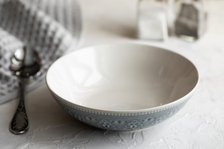 One white and gray bowl for soup and spoon on white table 免版税图像