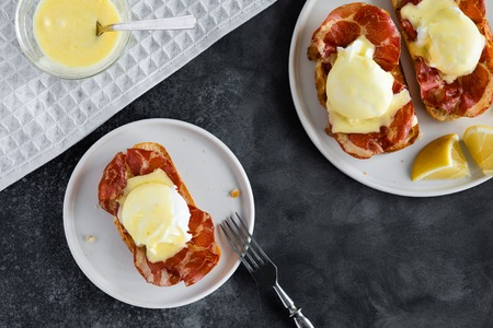 Top view of bruschetta with parma ham and Egg Benedict. Classic Eggs Benedict with bacon, hollandaise sauce, view from above 스톡 콘텐츠