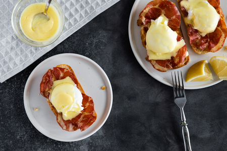 Top view of bruschetta with parma ham and Egg Benedict. Classic Eggs Benedict with bacon, hollandaise sauce, view from above 免版税图像