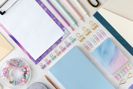 Flat lay of education, office or school stationery, mockup background on white desk. Flatlay and top view of pastel female office tools, pen and ink