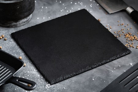 Black Slate board with Grill pan, knife with spices on a gray table