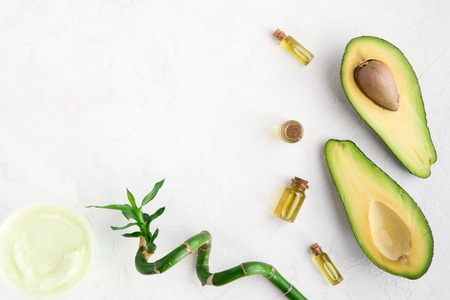 Top view of avocado and bamboo oil and scrub for spa beauty treatment use. Bottle of oil, green leaves and bamboo and fresh avocado on white background, flatlay 免版税图像