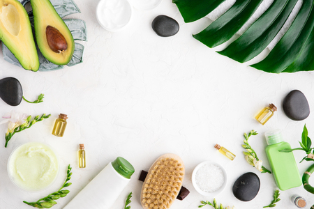 Spa beauty cosmetics of bottle, palm leaf, on white marble table, flat lay and top view. Copy space 免版税图像