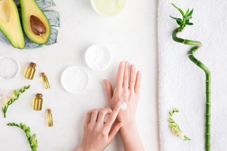 Top view and flat lay of woman puts cream on hands over white table with cosmetic products - avocado oil, cream and bamboo