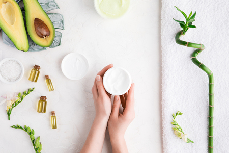 Top view and flat lay of woman holding cream on hands over white table with cosmetic products - avocado oil, cream and bamboo