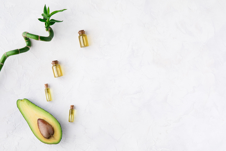 Top view of avocado and bamboo oil for spa beauty treatment or bodycare use. Bottle of oil, green leaves and bamboo and fresh avocado on white table background, flatlay