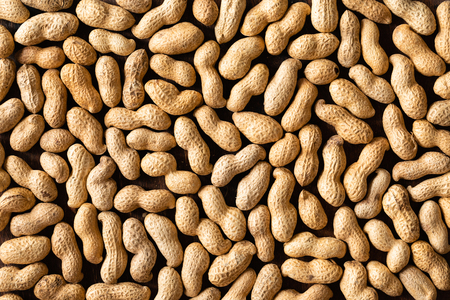 Top view of raw peanuts in shell, texture on wooden background. 免版税图像
