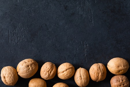 Natural walnut background pattern texture in-shell nuts, backdrop Walnuts in shell top view