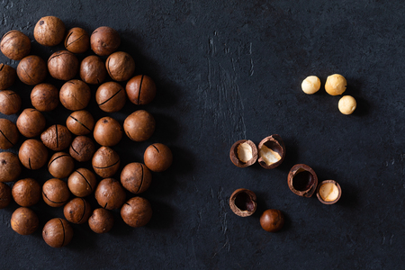 Top view of background texture of fresh natural unshelled raw macadamia nuts, full frame and flat lay