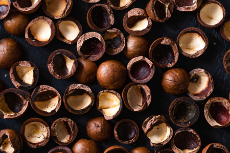 Top view of background texture of fresh natural shells of macadamia nuts, full frame and flat lay