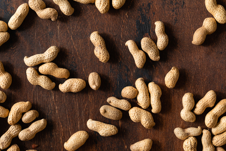 Top view of raw peanuts in shell, texture on wooden background. Stockfoto