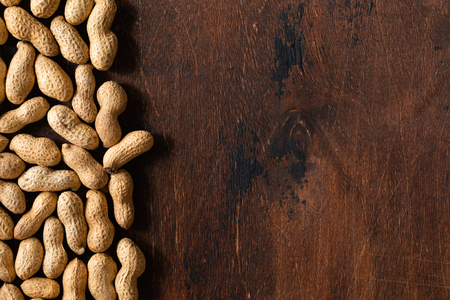 Top view of raw peanuts in shell with copy space, texture on wooden background. Stockfoto