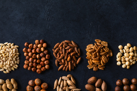 Various nuts on black stone table. Top view frame with copy space