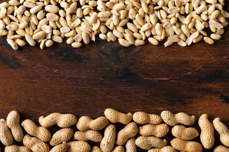 Top view of raw peanuts in shell and peeled as frame texture on wooden background. Stockfoto