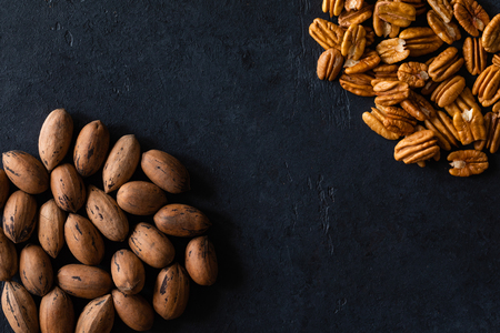 Natural pecan background pattern texture in-shell nuts, backdrop Pecans in shell top view