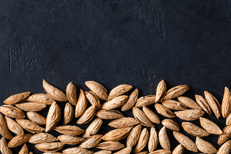 Top view of Background of raw peeled almonds on black table