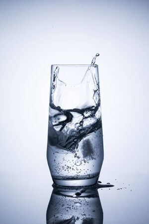 Glass of mineral sparkling water with ice on blue background 写真素材
