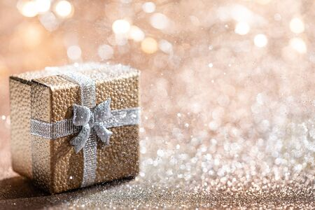 Gold gift box with magical light on glitter bokeh background. Christmas holidays. 写真素材