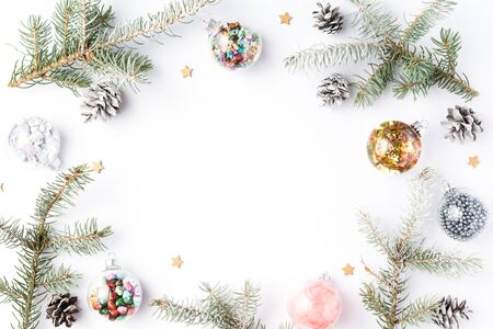 Christmas frame of fir tree spruce, gold christmas decorations on white background. Flat lay, top view, copy space. Winter holidays, New Year 2020 concept.