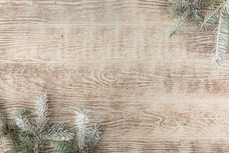 Christmas tree branch with pine cones on rustic wooden table. Winter background with copy space. Top view. Flat lay