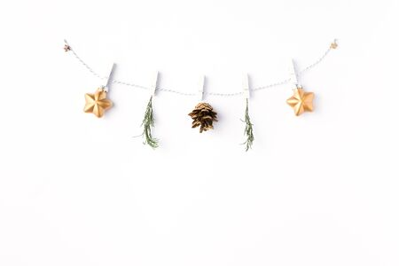 Christmas background. Flat lay of garland made of gold balls and fir tree branches over white background. Christmas, winter,New Year concept. Top view, copy space