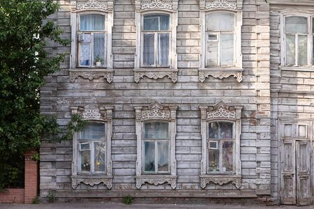 Old house with wooden shutters in Russia. Facade of a vintage house with blue gray walls