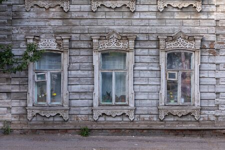 Old house with wooden shutters in Russia. Facade of a vintage house with blue gray walls 스톡 콘텐츠 - 129500058