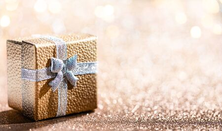 Gold gift box with magical light on glitter bokeh background. Christmas holidays. 免版税图像 - 129497995