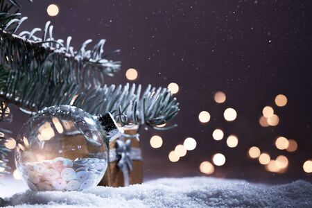 Christmas decorations banner. Snowy Fir-tree branch with Christmas lights bokeh at night. Panoramic background. Xmas composition. New Year 2020 holidays
