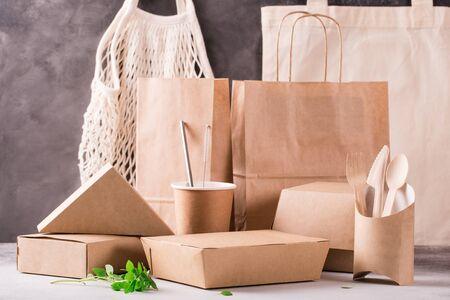 Pappbecher, Teller und Behälter für Catering und Street-Fast-Food. Umweltfreundliche Lebensmittelverpackungen und Baumwoll-Ökobeutel auf grauem Hintergrund mit Kopierraum. Pflege der Natur und Recyclingkonzept.