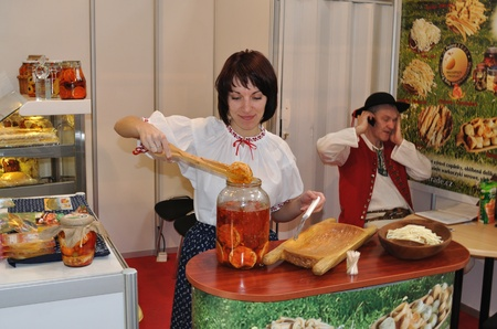 Warsaw, Poland - March 26, 2010 - Woman take out marinated cheese, from the jar - 14th International Food Service Trade Fair.  Stock Photo - 9073526