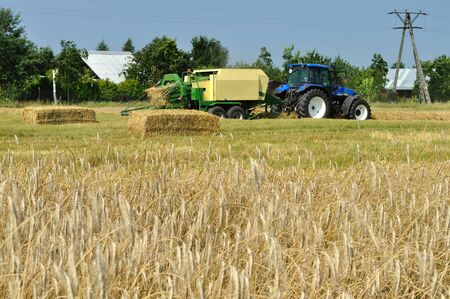 baler: tractor and baler machine, baling wheat straw. Stock Photo