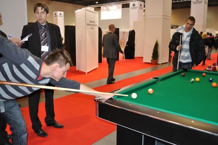 Warsaw, Poland - October 14, 2010 - visitor playing billiard, during SUREXPO 2010 - Salon of Entertainment Devices.