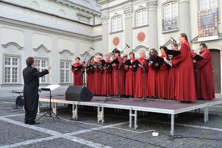 Warschau, Polen - 28 juni 2009 - Het Koor van Singing Society uit Saska Kepa zingen tijdens het concert in de rechtbank van het Warschau Koninklijk Kasteel. Artur Backiel dirigeert het koor.