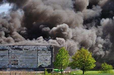 Rook stijgt van een magazijn brand.