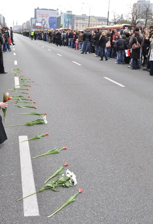 lugubrious: Warsaw, Poland - April 11, 2010 - Flowers on the street, before the car arrival with the coffin of Polish president, who was killed in a plane crash in Russia.