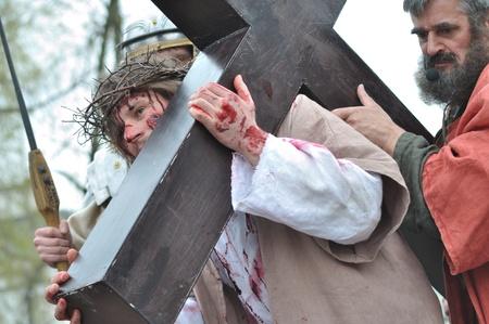 Gora Kalwaria, Polen - 17 april 2011 - Jezus wordt geholpen door Simon aan zijn kruis te dragen, tijdens de straatoptredens Mysterie van de Passie.