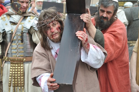easter triduum: Gora Kalwaria, Poland - April 17, 2011 - Jesus is helped by Simon to carry His cross, during the street performances Mystery of the Passion.