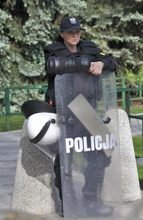 Warsaw, Poland - May 11, 2012 - Policewoman in riot gear, protecting a parliament building, during a protest of the Solidarity trade union against the pension reform.