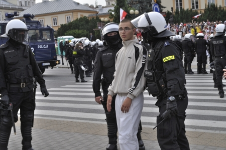 Warsaw, Poland - June 12, 2012 - Undefined soccer fan is moved by riot police protecting Russian fans marching to the National Stadium in Warsaw during the Euro 2012 soccer championship Group A match between Poland and Russia.