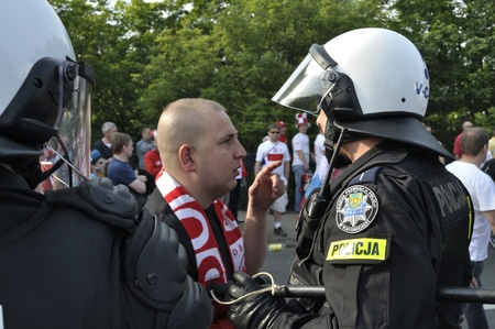 Warsaw, Poland - June 12, 2012 - Football fan talking to Riot Policeman during the UEFA EURO 2012 Group A match between Poland and Russia.
