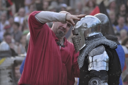 Warsaw, Poland - May 03, 2012 - Unidentified participant helps to remove the helmet during The International Festival of the Middle Ages