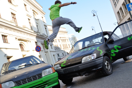 acrobat: WARSAW, POLAND - SEPTEMBER 17: Parkour acrobat jumping over the cars at the street of Warsaw. Editorial