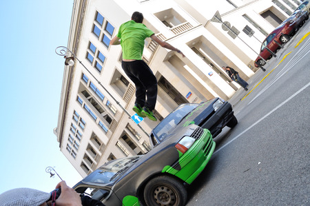 Warsaw, Poland - September 17, 2011:  Parkour acrobat jumping over the cars at the street of Warsaw.