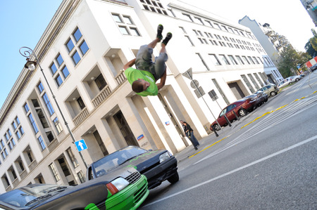acrobat: Warsaw, Poland - September 17, 2011:  Parkour acrobat jumping over the cars at the street of Warsaw.