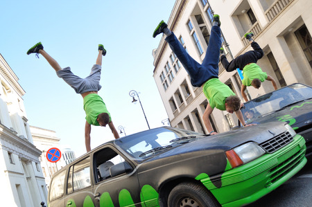 Warsaw, Poland - September 17, 2011: Freerun acrobats performing a handstand trick on the top of car at the street of Warsaw.