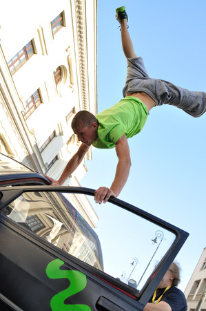 fleeing: Warsaw, Poland - September 17, 2011: Freerun acrobat performing a handstand trick on the top of car at the street of Warsaw.