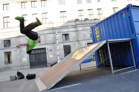 acrobat: Warsaw, Poland - September 17, 2011: Freerun acrobat performing somersaults flips at the street of Warsaw. Editorial