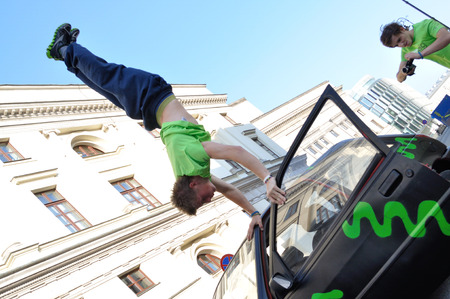 Warsaw, Poland - September 17, 2011: Freerun acrobat performing a handstand trick on the top of car at the street of Warsaw.