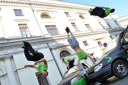 Warsaw, Poland - September 17, 2011:  Parkour acrobats jumping over the cars at the street of Warsaw. Editorial